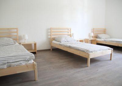 Monteurzimmer Einzelbetten mit Nachttisch und Lampe