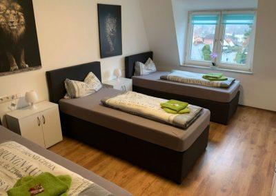 Monteurzimmer Einzelbetten mit Lampen und Tischen