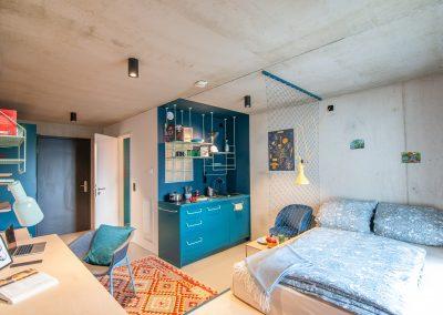 Schlafzimmer mit Doppelbett und Küchenzeile