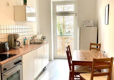 Küche mit Herd, Sitzgruppe und Balkon