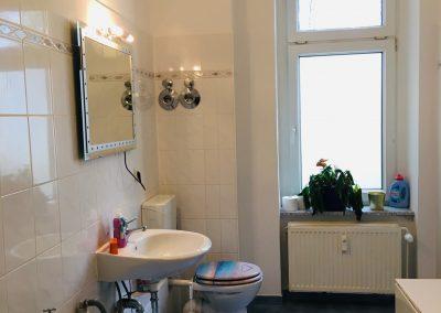 Badezimmer mit Dusche, Waschmaschine und Toilette