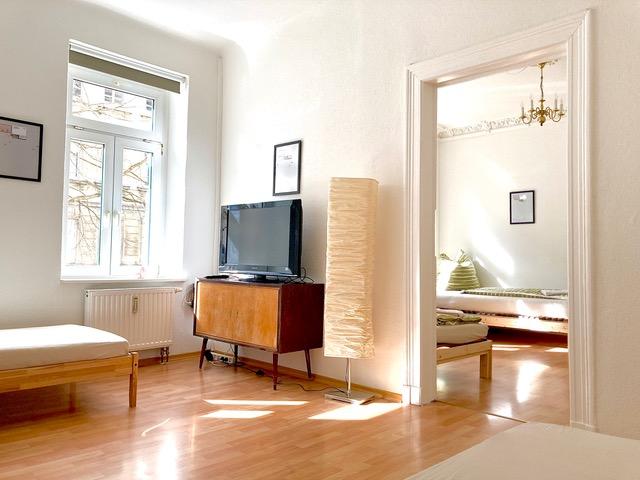 Schlafzimmer mit Betten, Stühlen und TV